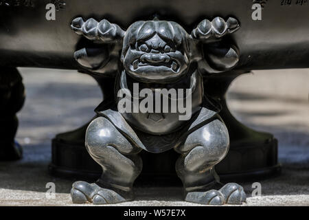 Carved figure on a giant urn at Gotokuji Temple in Setagaya city, Tokyo, Japan. - Stock Photo