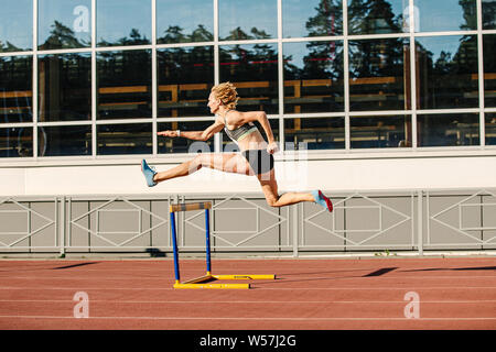 woman athlete runnner running hurdles in summer athletics competition - Stock Photo