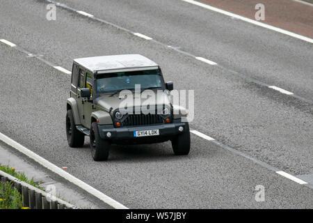 2014 Jeep Wrangler Sahara Un-Ltd CR; M6, Lancaster, UK; Vehicular traffic, transport, modern, saloon cars, north-bound on the 3 lane motorway highway. - Stock Photo