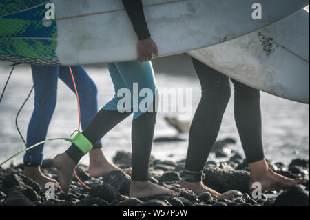 Close up view of three surfer at the beach with board walking barefoot. Close-up view of young legs of sportive men at the beach. Group of young boy p