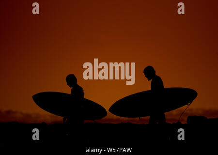 Silhouettes of surfers walking along a beach at sunset. Athletes carrying their surfboard on ocean sunset. Two friends with board in a orange summer e - Stock Photo