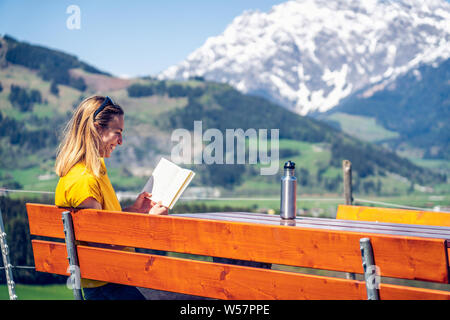 Young beautiful and happy girl reading a book on a bench, mountain range and greenery in the background. - Stock Photo