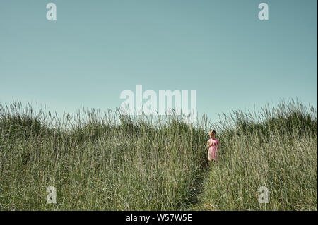Field trip concept with pretty little girl in pink dress standing on trail among tall grass on Grotta island in summer - Stock Photo
