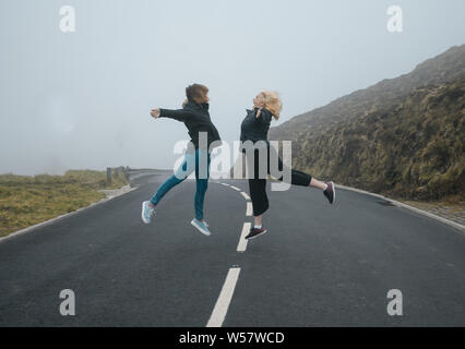 Two young women jumping on a road with fog - Stock Photo