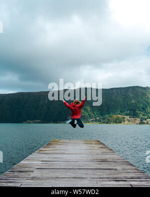 Young woman jumping on the jetty of a lake - Stock Photo