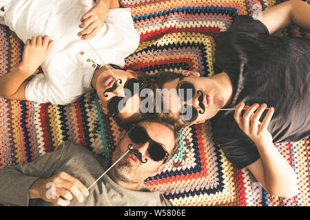 Father and two sons enjoying together lying on a colorful blanket. Tree men of different ages smiling playing with fake mustache. Top view of a couple - Stock Photo