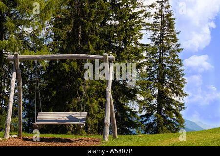 Holzbank Schaukel vor Wald in den Alpen - Stock Photo