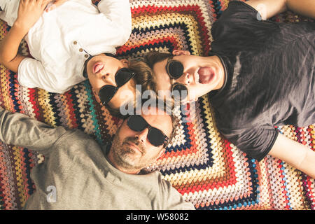 Father and two sons enjoying together lying on a colorful blanket. Tree men of different ages with black sunglasses. Top view of a couple of teen maki - Stock Photo