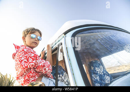 Handsome teenage boy with sunglasses posing charming out the window of the vintage van dressed as a flower child, hippie. Concept of freedom and light - Stock Photo
