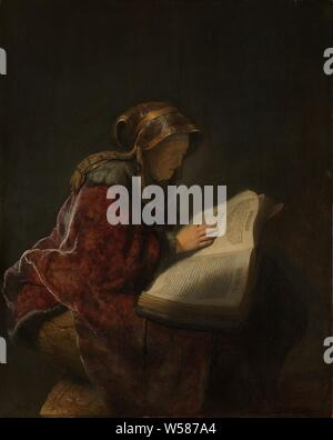 Old Woman Reading, Probably the Prophetess Anna An Old Woman Reading, Probably the Prophetess Hannah, An old woman, probably Rembrandt's mother, Neeltgen Willemsdr van Zuydtbroeck (d. 1640), probably presented as the prophetess Anna. A seated old woman reading a large book lying open on her lap, reading the Bible or other religious books, old woman, Rembrandt van Rijn (mentioned on object), 1631, panel, oil paint (paint), h 60 cm × w 48 cm - Stock Photo