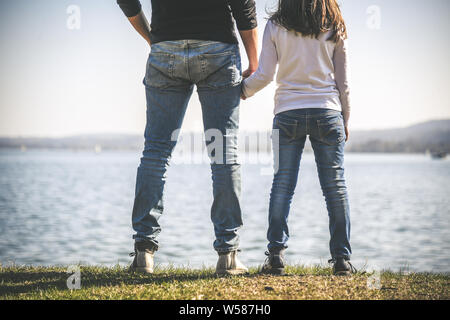 Father and daughter holding hands near the sea. two people standing on the seashore in a beautiful sunny day. Dad and little girl looking at horizon.