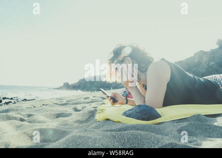 Beautiful girl relaxing at the beach reading news online. Portrait of a woman lying on a towel in sunny summer evening Female chatting outdoor at suns