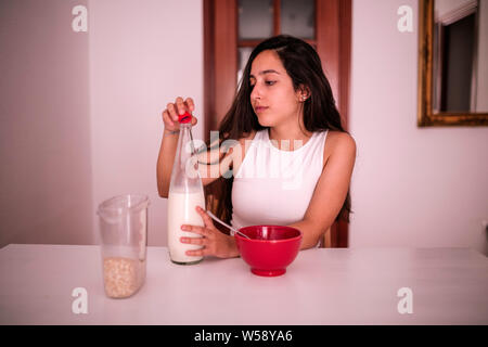 Teen girl eating milk with cereal - Stock Photo