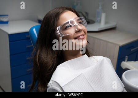 happy smiling young woman patient lying on dental chair wearing safety glasses under the medical lamp in clinic - Stock Photo