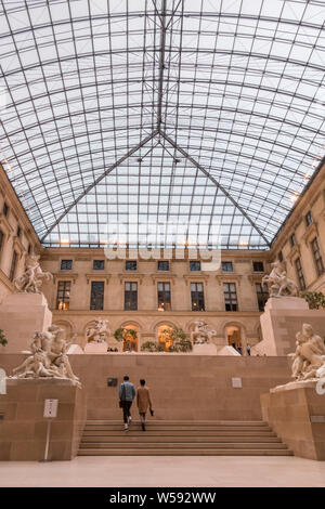 Great picture of the sculpture garden known as Cour Marly in the Richelieu wing of the Louvre Museum. Two visitors are going up the stairs of the... - Stock Photo