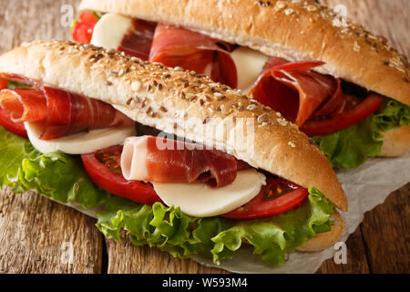 Delicious Italian sandwiches with prosciutto ham, mozzarella cheese and vegetables close-up on the table. horizontal - Stock Photo