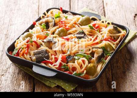Traditional pasta dish with roasted eel, olives, pepper and tomato sauce closeup on a plate on the table. horizontal - Stock Photo