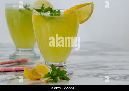 Refreshing drinks for summer, cold sweet and sour lemonade juice  in the glasses garnished with sliced fresh lemons - Stock Photo
