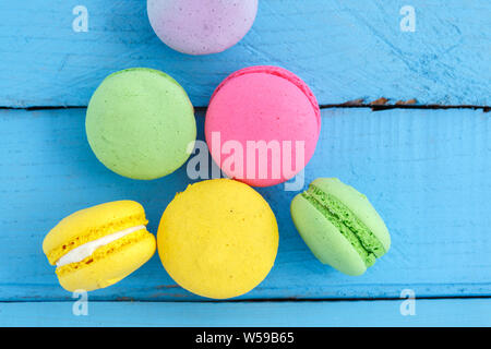 colorful macaroni or macaroons cookies on blue wooden vintage background. top view - Stock Photo