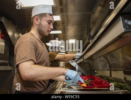 190725-N-KG461-1053  ARABIAN GULF (July 24, 2019) Operations Specialist 3rd Class Mario Cortez, from La Puente, Calif. assigned to amphibious assault ship USS Boxer (LHD 4), serves food to Sailors and Marines in the mess deck galley, July 25, 2019. Boxer is part of the Boxer Amphibious Ready Group and 11th Marine Expeditionary Unit and is deployed to the U.S. 5th Fleet area of operations in support of naval operations to ensure maritime stability and security in the Central Region, connecting the Mediterranean and the Pacific through the Western Indian Ocean and three strategic choke points. ( - Stock Photo