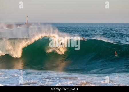 A surfer surfs a large wave at The Wedge in Newport Beach, California - Stock Photo