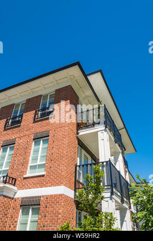 The corner of brand new apartment building on blue sky background - Stock Photo