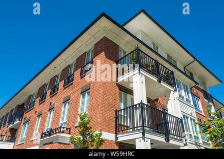 The top of brand new apartment building on blue sky background - Stock Photo