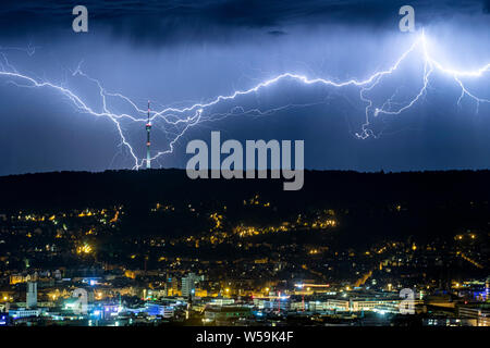 Stuttgart, Germany. 27th July, 2019. Lightnings twitch at night behind the illuminated city on the horizon, and strike near the television tower. In the Stuttgart area it thundered in the night to Saturday, the 27.07.2019 violently. Credit: Simon Adomat/dpa/Alamy Live News - Stock Photo