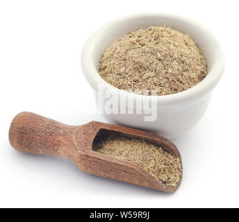 Liquorice stick and ground in a small bowl over white background - Stock Photo