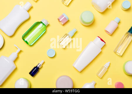 Top view of different cosmetic bottles and container for cosmetics on yellow background. Flat lay composition with copy space. - Stock Photo