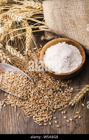 still life. White flour in the wooden bowl and some ears of wheat on the rustic wooden table - Stock Photo