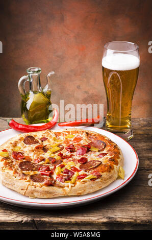 on the rustic wooden table a pizza stuffed with salami and hot pepper and a glass of beer - Stock Photo