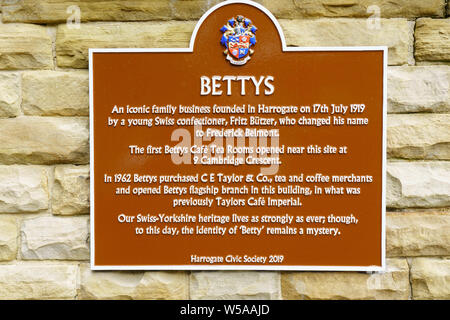 New brown and white metal plaque on the exterior of Betty's Tearooms,Harrogate,North Yorkshire,England. - Stock Photo