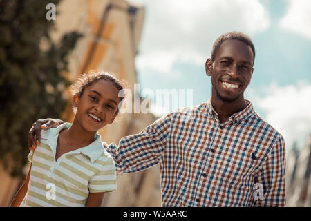 Positive delighted international family looking at camera - Stock Photo