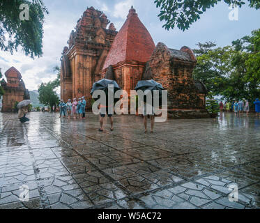 Nha Trang,Viet Nam , 27 July 2019. A downpour at the Po Nagar Cham Towers, One of the more important Cham sites in VietNam ,dating back to the 8th century when it was built by the kings of the Cham principalityKauthara. Tourist enjoyng the site with umbrellas and plastic clothing. Paul Quezada-Neiman/Alamy Live News - Stock Photo