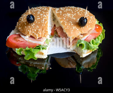 Tasty sesame seed sandwich stuffed with ham, cheese, fresh salad, red tomatoes and black olives on a black background with reflection - Stock Photo