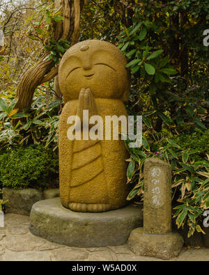 Little stone statue of a small praying monk in a funny looking shape with rich details, Hase-dera Kamakura Japan 2018 - Stock Photo
