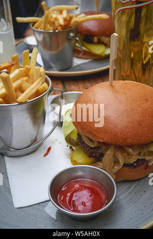 Close-up view of a beef burger with cheddar, pickles, lettuce and onions with a French fries and ketchup and mayo sauces. Portrait format. - Stock Photo