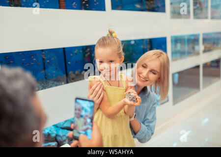 Daddy taking photo of daughter holding little hamster in hands - Stock Photo