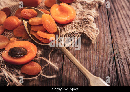 Dried apricots arranged on a fabric and spoon. Composition in the old style - Stock Photo