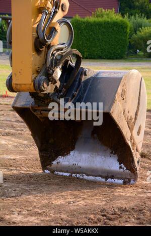 excavator bucket macro shot, dredger bucket close-up view of excavator on construction site - Stock Photo