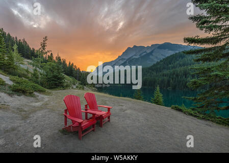 Sunrise over Red Chairs at Two Jack Lake in Banff National Park, Alberta, Canada - Stock Photo