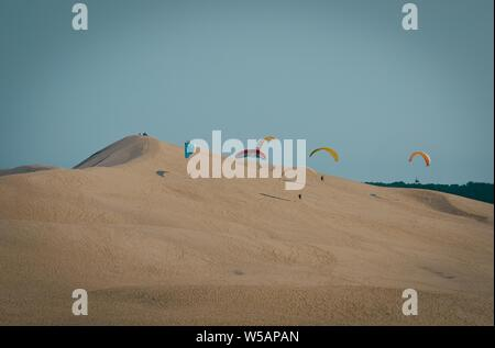 A long-range shot of paragliders landing on a sand dune with clear blue sky in the background - Stock Photo