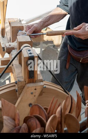 An artisan carves a piece of wood using a manual lathe - Stock Photo