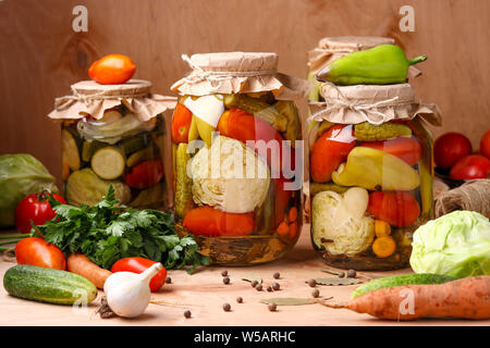Assorted pickled vegetables in jars: cucumbers, tomatoes, cabbage, zucchini and peppers with garlic, dill and bay leaves in jars on a wooden backgroun - Stock Photo