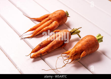 Flat lay Some ugly curved carrots on white wooden background. - Stock Photo