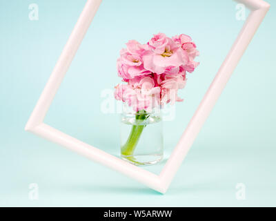 White landscape frame mockup with flowers in styled vase near blue wall. Empty frame mock up for presentation design. Template framing for modern art - Stock Photo
