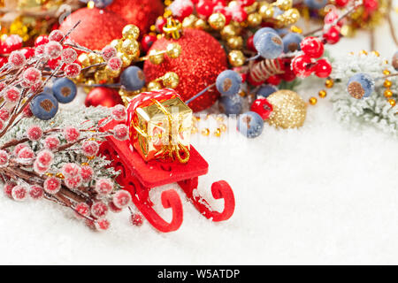 Christmas background with red Santa sleigh and Xmas gift on white snow with empty copy space - Stock Photo