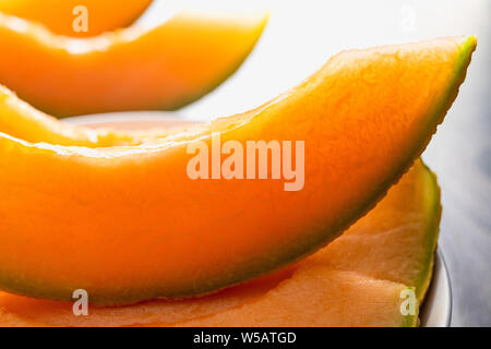 Cantaloupe Melon. Orange Cantaloupe Melon Slices on a Chopping Board Close Up on a Kitchen Table - Stock Photo