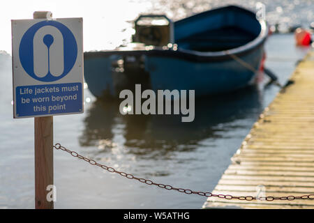 Warning Sign that says Life jackets must be worn beyond this point with a boat in the background on a lake in Hornsea - Stock Photo
